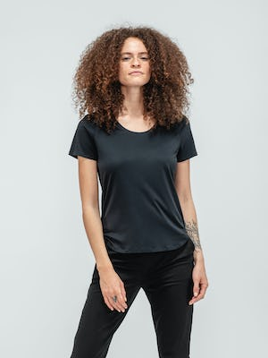 Woman with curly hair wearing black short sleeve luxe touch tee and black kinetic pull on pants