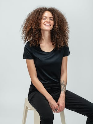 Woman with curly hair wearing black short sleeve luxe touch tee and sitting on a stool