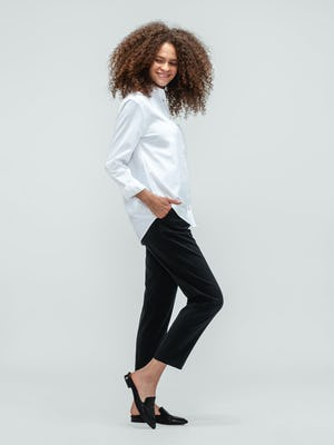 Woman with curly hair looking over shoulder wearing the white aero zero boyfriend button down shirt and swift drape pants in black