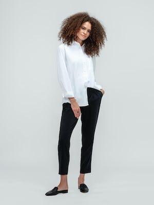 Woman standing wearing white aero zero button down shirt and black swift drape pants with black flats