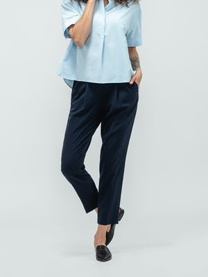 Woman with hands in pocket of navy swift drape pants and black flats