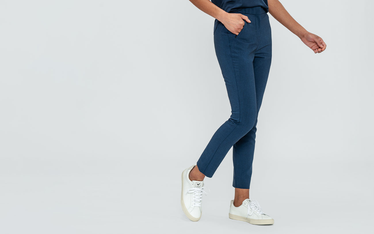 women's indigo heather velocity tapered pant model facing off-center with hand in pocket