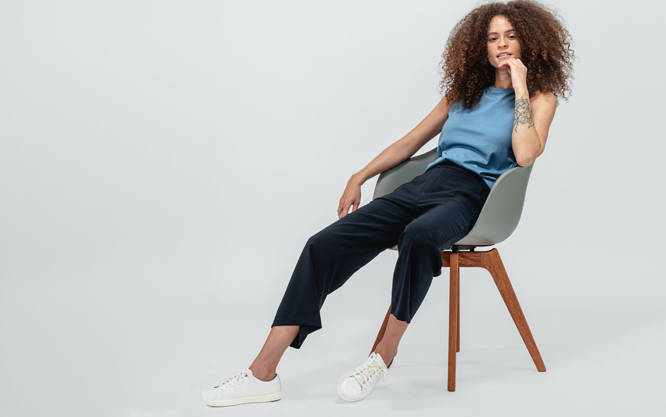 model wearing storm blue composite tank and navy swift wide leg pull on pant lounging in chair
