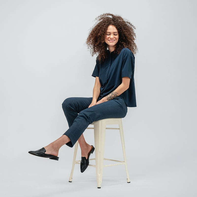 Women's Juno Boxy Blouse and Velocity Tapered Pant on model sitting on a chair