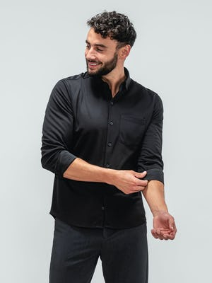 Man wearing the apollo sport shirt in black rolling up sleeves