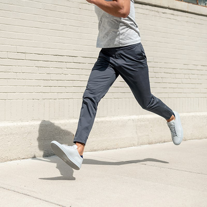 Man running in front of brick wall wearing grey pants