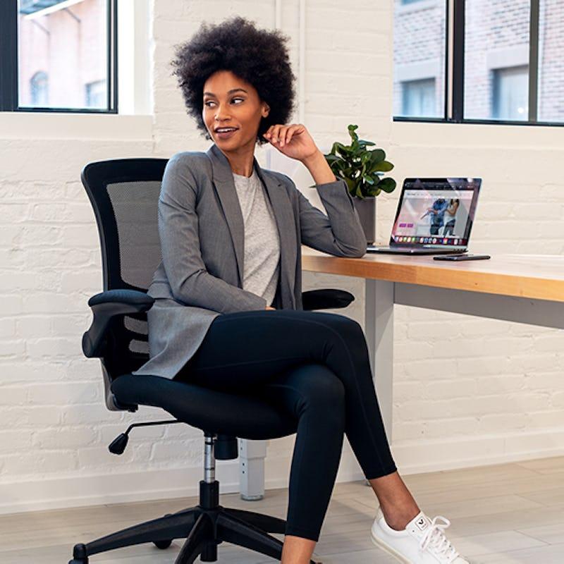 Woman sitting in desk wearing black Joule leggings and a grey blazer