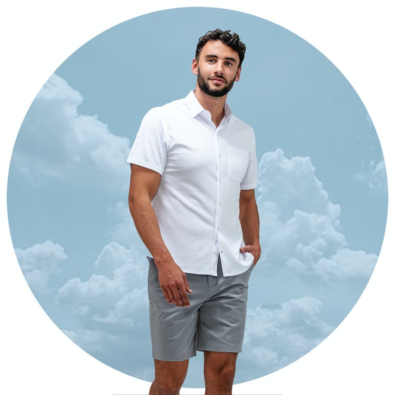 Man wearing a short sleeve white shirt and grey shorts with a background of clouds