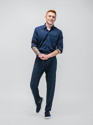 model wearing azurite heather velocity pant and navy apollo sport shirt walking forward