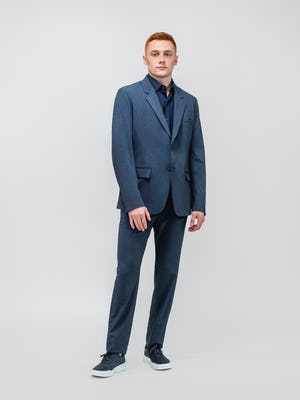 model wearing men's azurite heather velocity suit and navy apollo sport shirt facing forward