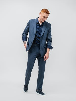 model wearing men's azurite heather velocity suit and navy apollo sport shirt walking forward with hand in pants pocket and jacket sleeves cuffed