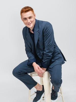 model wearing men's azurite heather velocity suit and navy apollo sport shirt sitting on stool with jacket sleeves cuffed