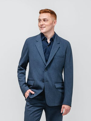 model wearing men's azurite heather velocity suit and navy apollo sport shirt facing forward with hand in pants pocket