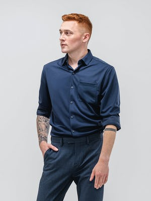 model wearing men's navy apollo sport shirt and azurite heather velocity pant facing forward with hand in pocket
