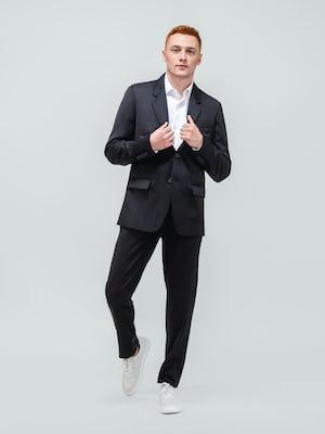 model wearing men's black wool velocity merino suit and white aero zero dress shirt walking forward with hands on lapels