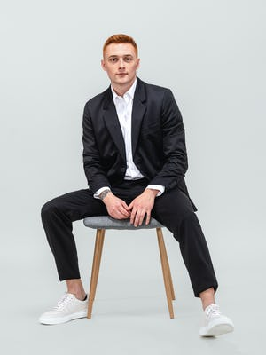 model wearing men's black wool velocity merino suit and white aero zero dress shirt sitting in a chair with hands in lap
