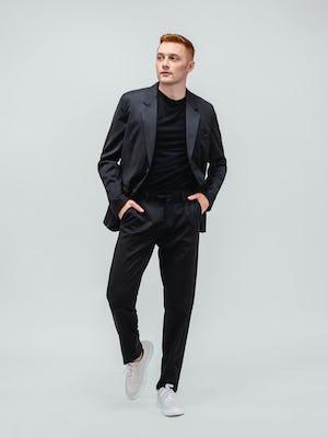 model wearing men's black wool velocity merino suit and black atlas crew neck tee walking forward with hands in pockets