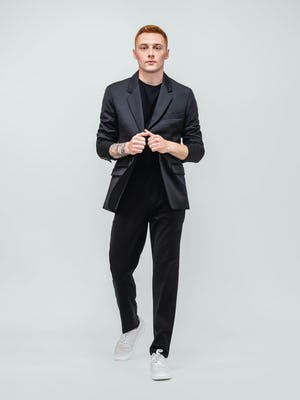 model wearing men's black wool velocity merino suit and black atlas crew neck tee walking forward with hands on lapels