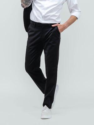 close up of model wearing men's black wool velocity merino suit and white aero zero dress shirt facing forward with hand in pocket