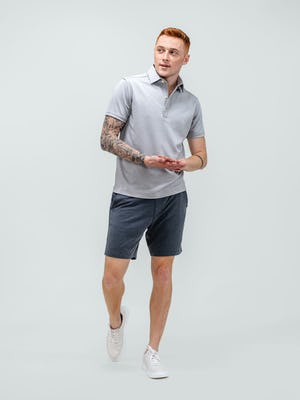 model wearing men's dark charcoal fusion terry shorts and grey heather apollo polo walking forward with hands clasped