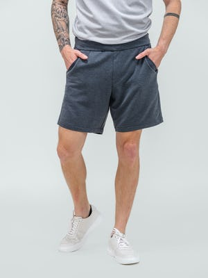 model wearing men's dark charcoal fusion terry shorts facing forward with shirt tucked in and hands in pockets