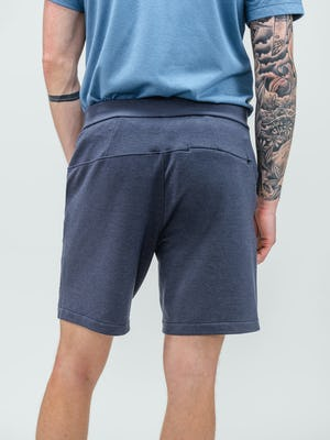 rear shot of model wearing men's navy fusion terry shorts and storm blue composite merino short sleeve henley shirt tucked in