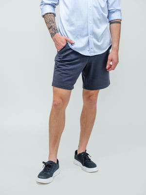 model wearing men's navy fusion terry shorts and blue heather stripe hybrid button down facing forward with cuffs rolled up and hand in pocket