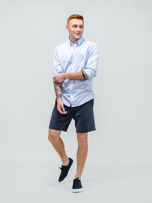 model wearing men's navy fusion terry shorts and blue heather stripe hybrid button down walking forward while rolling up cuffs