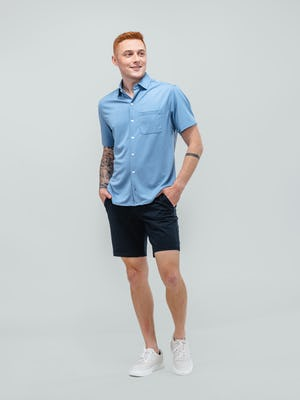 model wearing men's steel blue apollo short sleeve sport shirt and navy kinetic shorts facing forward with hands in pockets