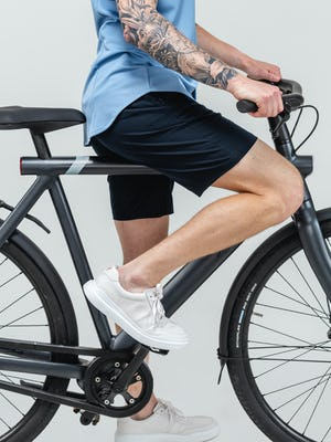 model wearing navy kinetic shorts and steel blue apollo sport shirt on a bicycle