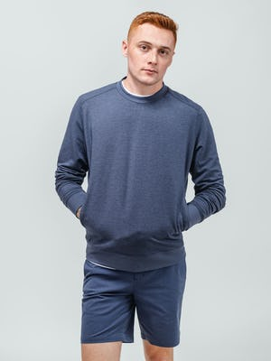 model wearing navy fusion terry sweatshirt and slate blue kinetic shorts with hands in pockets