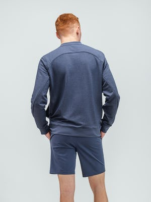 model wearing navy fusion terry sweatshirt and slate blue kinetic shorts facing away hands in short pockets