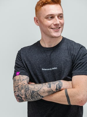 male model wearing charcoal heather science for better tee close up with arms crossed