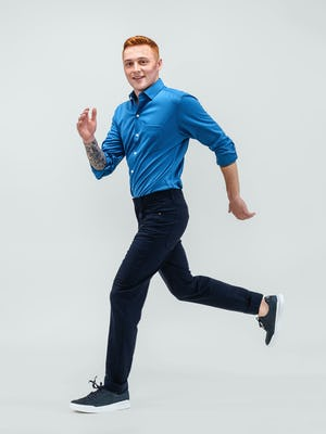 model wearing royal blue apollo sport shirt and navy heather kinetic twill 5 pocket pant hand in pocket running with sleeves rolled