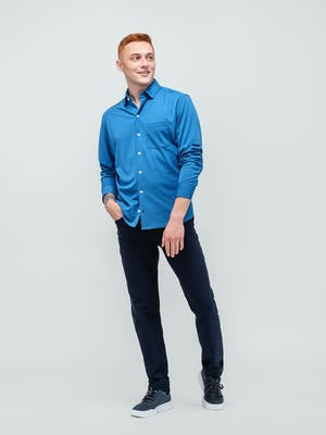 model wearing royal blue apollo sport shirt and navy heather kinetic twill 5 pocket pant hand in pocket facing forward with sleeves rolled