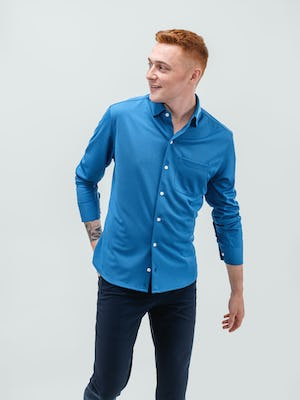 model wearing men's royal blue apollo sport shirt and kinetic twill 5-pocket pant facing forward with hand in back pocket and sleeves pulled up