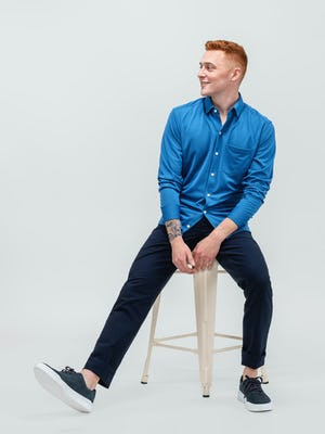 model wearing royal blue apollo sport shirt and navy heather kinetic twill 5 pocket pant hand in pocket sitting with sleeves pulled up
