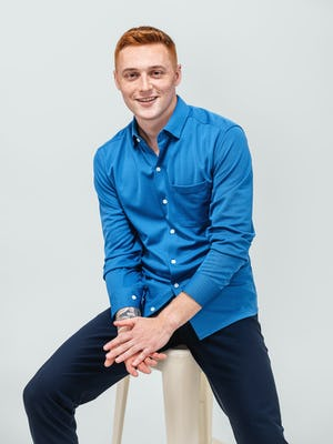 model wearing men's royal blue apollo sport shirt sitting with hands clasped and sleeves pulled up