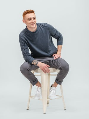 model wearing dark charcoal fusion terry sweatshirt and medium grey pace tapered chino sitting on a stool with pant legs cuffed and sleeves pulled up looking to the side