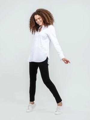 model wearing women's white aero zero band collar tunic and black fusion straight leg pant facing sideways