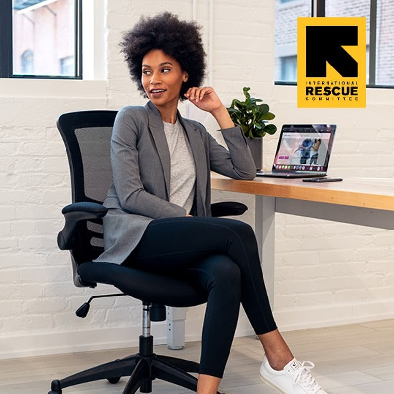 Woman sitting in office chair in front of a laptop wearing a grey blazer and black leggings