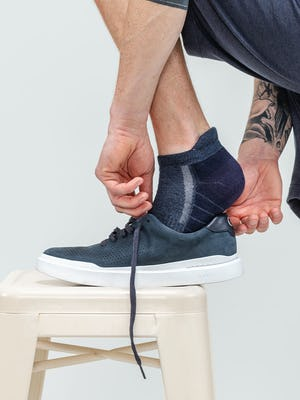 close up of model wearing midnight/navy atlas ankle sock with foot on a stool putting on a sneaker