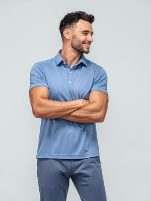 model wearing ocean oxford apollo polo and indigo heather kinetic jogger with arms crossed looking to the side