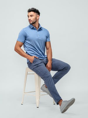 model wearing ocean oxford apollo polo and indigo heather kinetic jogger sitting on a stool with hand in pocket looking to the side