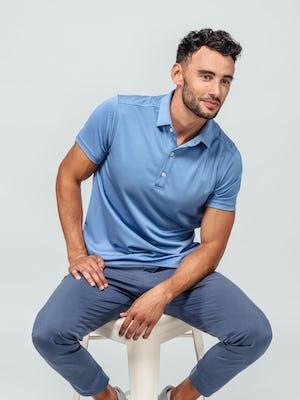 model wearing ocean oxford apollo polo and indigo heather kinetic jogger sitting on a stool