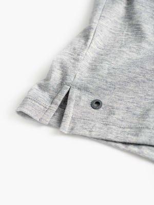 men's pale grey heather composite merino zip polo zoomed shot of split hem and metal degree symbol