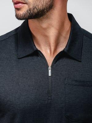 close up of model wearing black composite merino zip polo