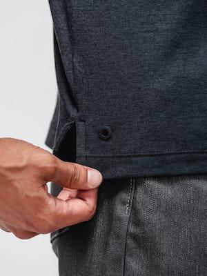 close up of model wearing black composite merino zip polo and dark grey chroma denim touching hem
