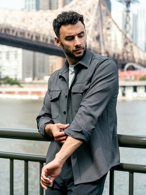 model wearing men's charcoal tweed fusion overshirt and black pace tapered chino standing outside rolling up sleeves