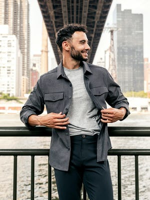 model wearing men's charcoal tweed fusion overshirt and black pace tapered chino and pale grey heather composite merino tee standing outside under a bridge with sleeves rolled